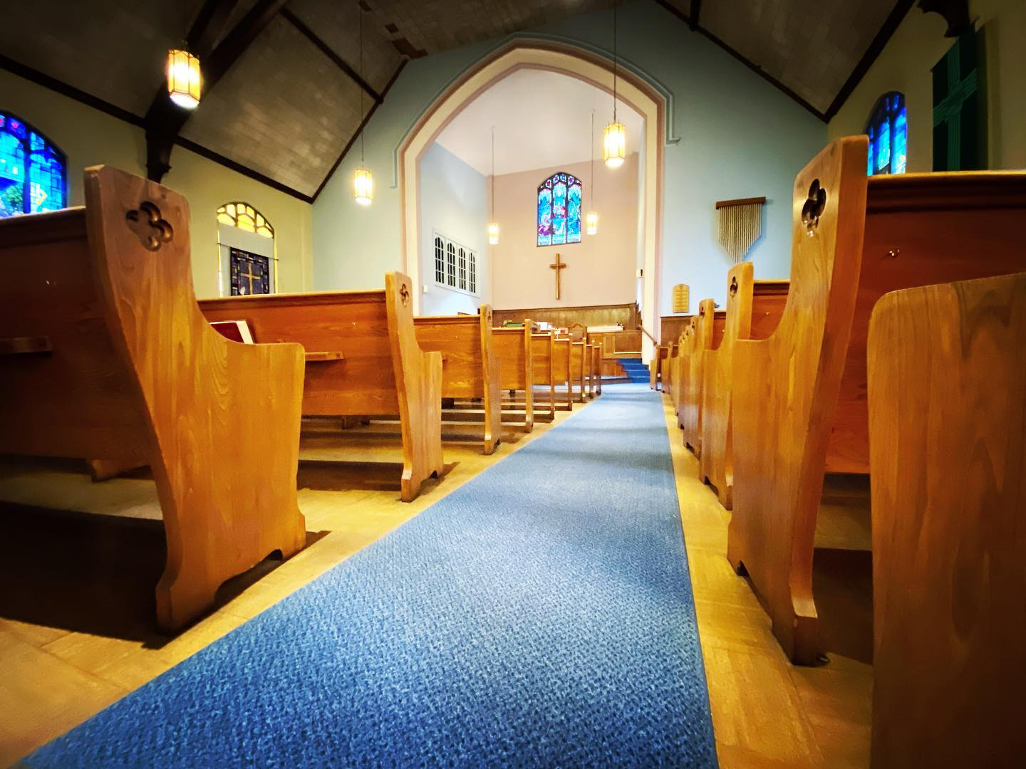 A blue carpeted aisle with wood pews on either side, leading to the altar.